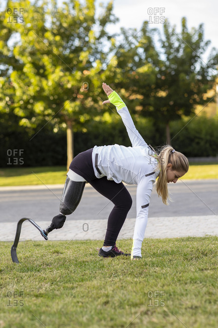 Side view of professional female runner with leg prosthesis preparing for explosive start during training in park