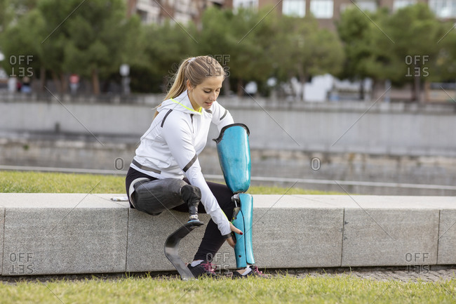 Calm female runner in sportswear sitting with leg prosthesis in city and preparing for training
