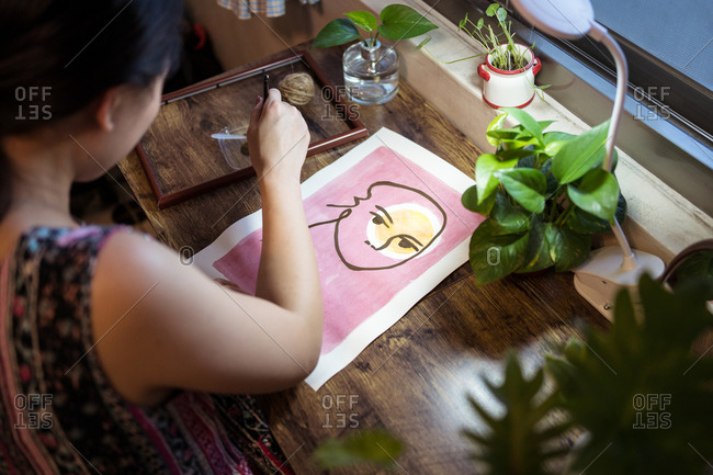 High angle side view of unrecognizable Asian female artist sitting at wooden table and creating picture on paper with paint and brush
