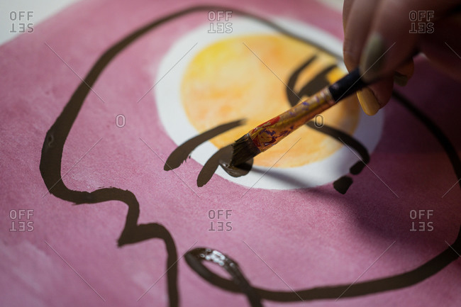 Closeup view of crop unrecognizable female artist creating picture with paint and brush on canvas in workshop