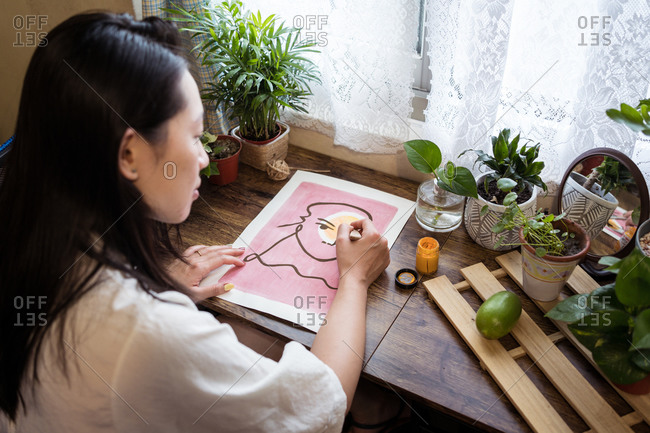 High angle side view of Asian female artist sitting at wooden table and creating picture on paper with paint and brush
