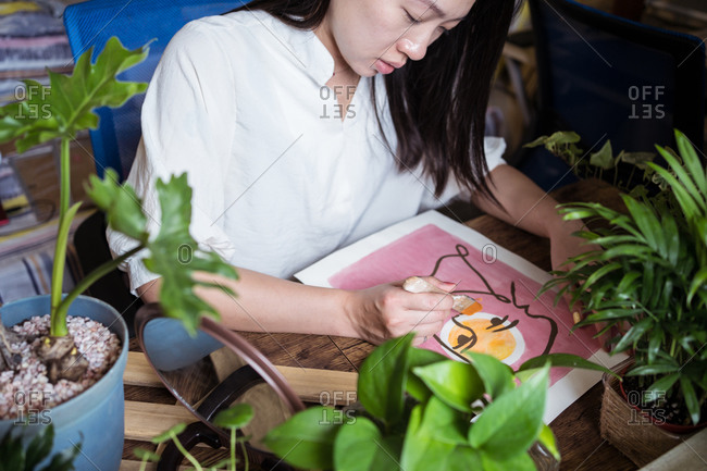Focused Asian female artist sitting at wooden table and creating picture on paper with paint and brush
