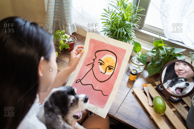From above of smiling Asian female artist reflecting in mirror sitting at table and admiring amazing artwork