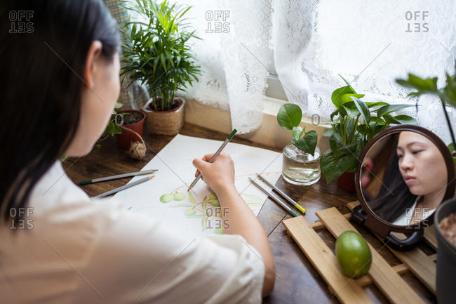 From above of talented Asian female artist drawing with pencil on paper while sitting at table at home