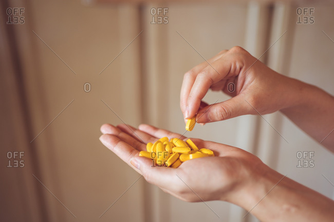 From above of crop palm of anonymous person demonstrating pile of yellow vitamin pills for healthy lifestyle concept