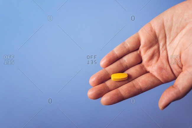 From above of crop palm of anonymous person demonstrating yellow vitamin pill for healthy lifestyle concept against blue background