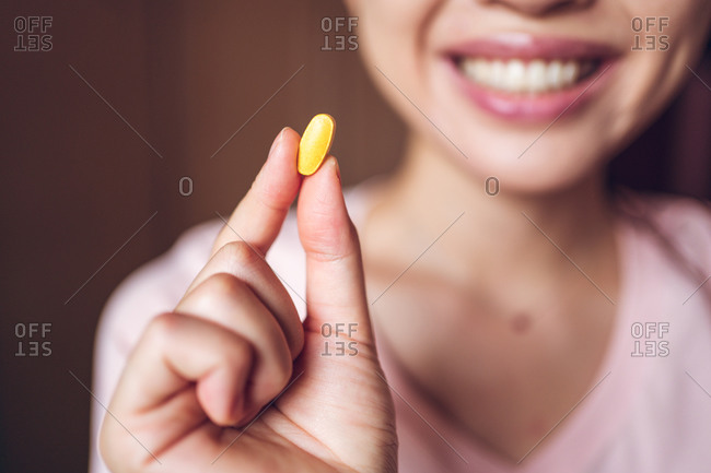 Crop unrecognizable cheerful healthy female showing bright yellow vitamin pill during health care routine at home
