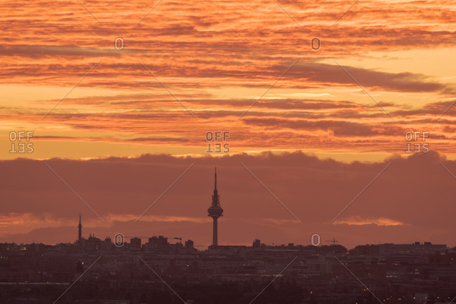 Picturesque view of buildings under vibrant orange sunset sky in city of Madrid