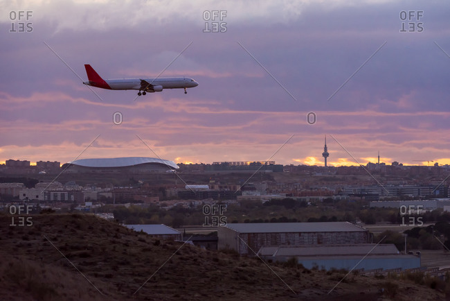 Peaceful view of contemporary aircraft flying over Madrid on background of sundown sky