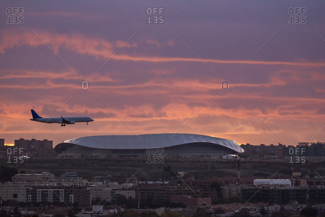 November 15, 2019: Peaceful view of contemporary aircraft flying over Madrid on background of sundown sky