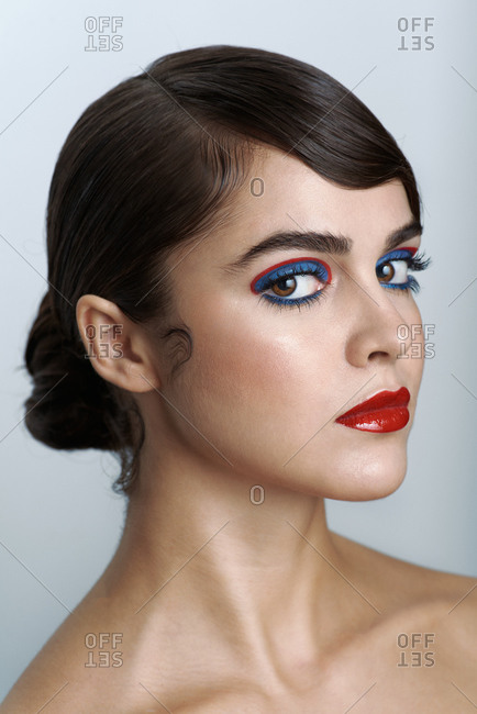 Attractive sensual young brunette with bright colorful eyeshadows and glossy red lips looking at camera against gray background