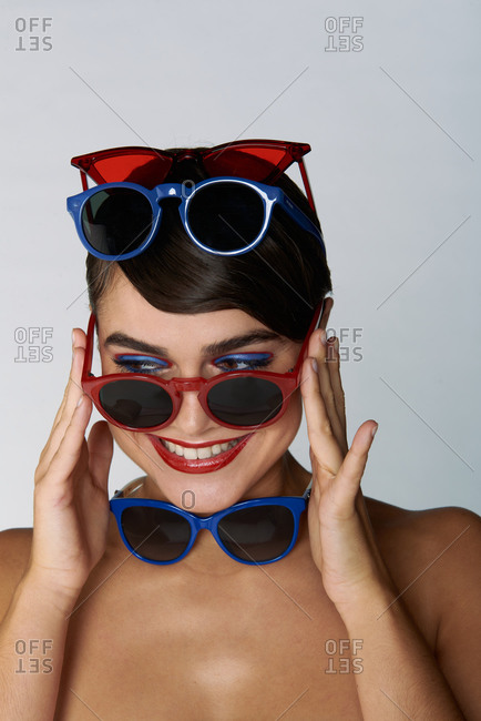 Fashionable young brunette model with red lips and various trendy sunglasses with colorful frames keeping hand near open mouth against light gray background