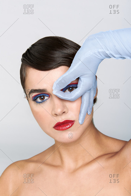 Beautiful young bare shouldered brunette with glamorous bright makeup and elegant gray gloves looking at camera through fingers in light studio