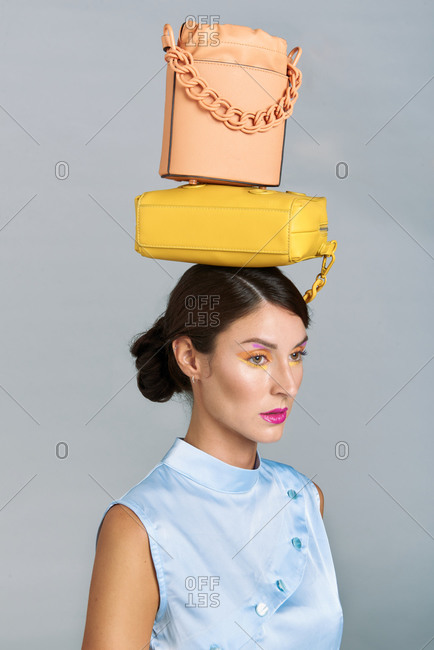 Stylish young brunette model with bright makeup and colorful modern leather handbags on head standing against gray background