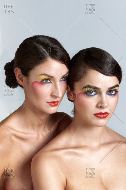Serious bare shouldered young brunette models with perfect skin and creative colorful glamorous makeup standing together against light gray background