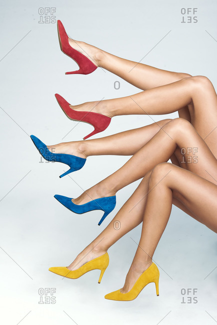 Side view of crop legs of unrecognizable female models wearing stylish bright multicolored high heeled shoes on white background