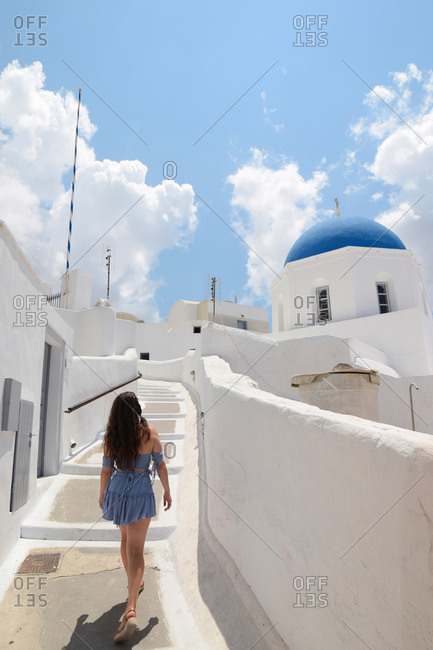 Back view of female tourist in summer dress walking up narrow street with white buildings while enjoying vacation on Santorini