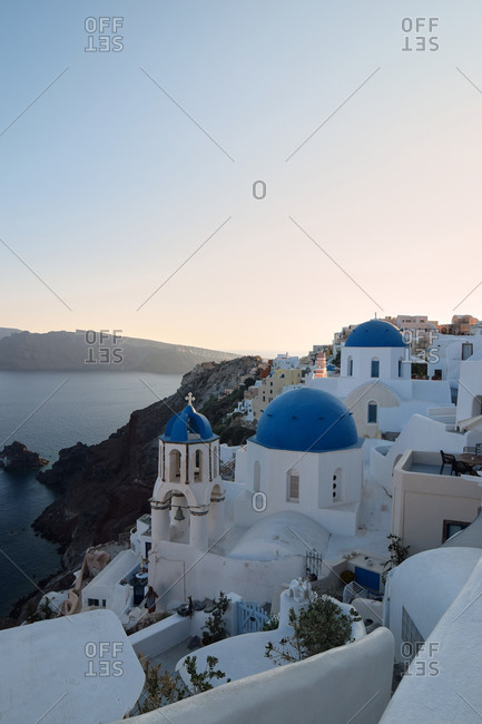 Spectacular scenery of city with white church with round shaped blue dome located in front of sea on Santorini