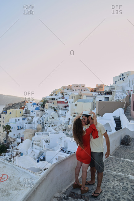 Loving traveling couple kissing at sundown while standing on balcony on Santorini and enjoying vacation together