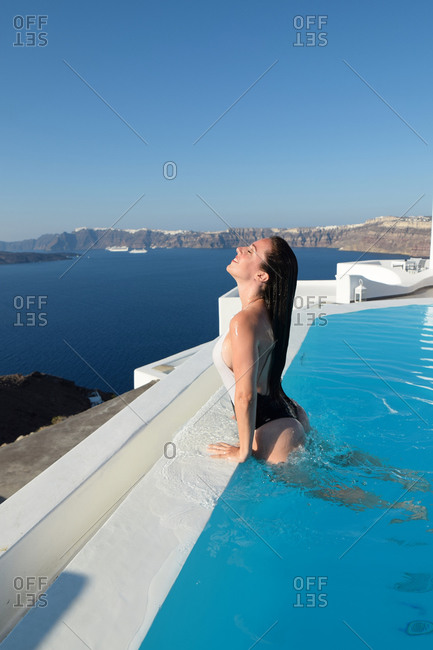 Side view of delighted female tourist in swimsuit and with wet hair leaning on poolside of swimming pool and enjoying vacation on Santorini