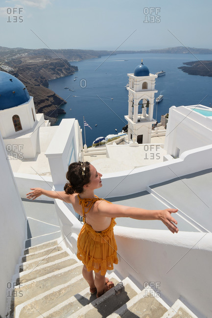 From above of delighted female tourist standing with outstretched arms on stairs of white building and enjoying cityscape of Santorini during summer holiday