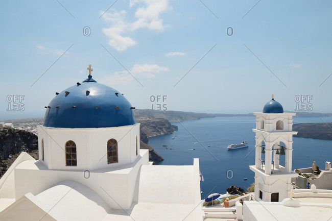 Amazing view of cityscape of Santorini with white church on background of sea on sunny day