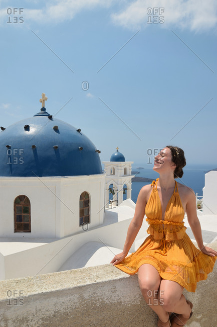 Carefree female tourist in yellow dress sitting on stone border and relaxing on sunny day during summer holiday on Santorini