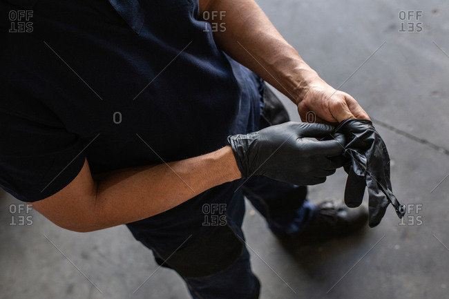 From above anonymous male employee putting on latex gloves during work in garage