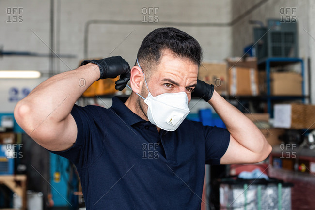 Male employee putting white face mask for work in garage