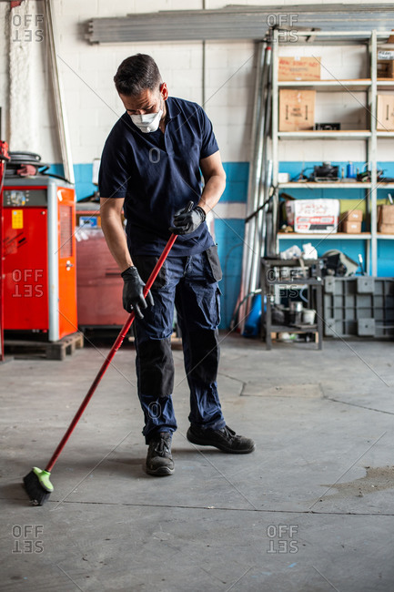 Low angle of man in uniform sweeping floor with broom while working in garage