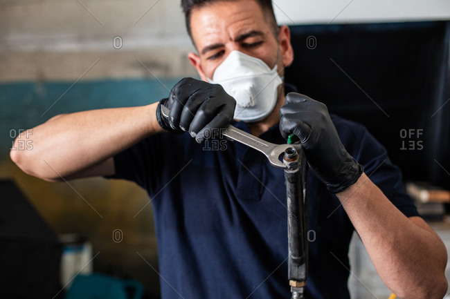 Male mechanic in respirator and latex gloves screwing nut on nozzle with spanner while working in professional workshop