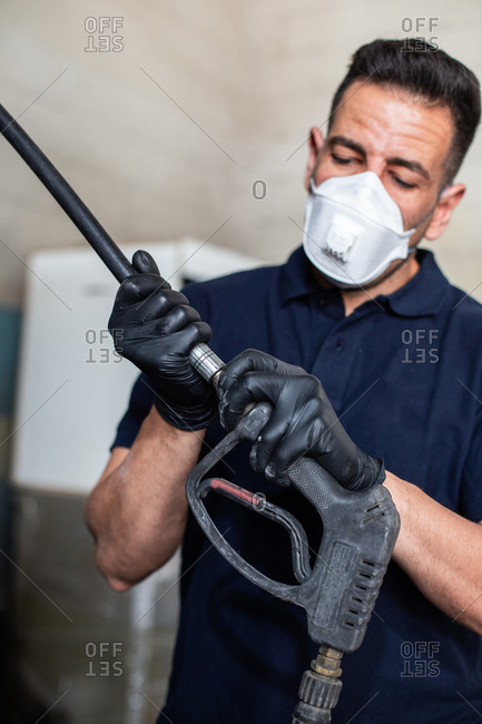 Adult man in respirator and latex gloves attaching nozzle to hose while working in garage