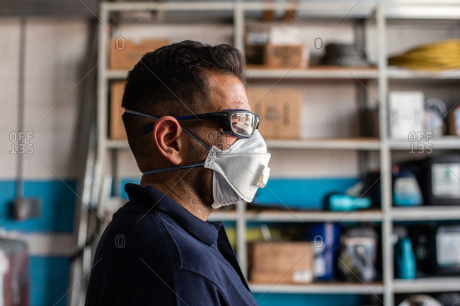 Adult man in respirator and protective goggles and looking away during work in garage