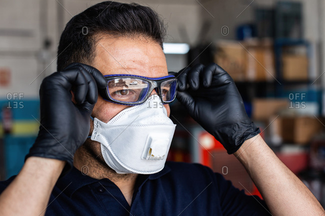 Adult man in latex gloves and respirator putting on protective goggles and looking at camera during work in garage