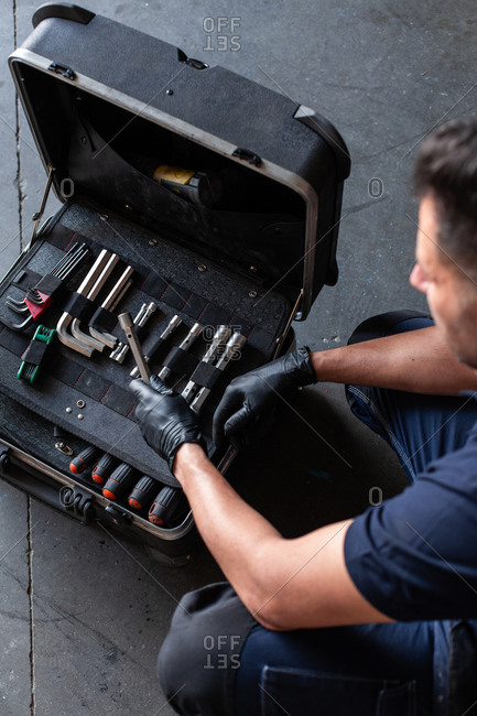 From above male technician picking screwdriver bits from tool box while working in garage