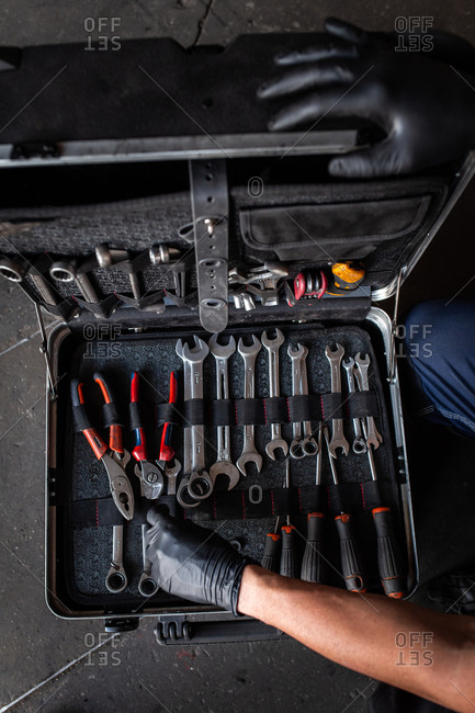 Front view of unrecognizable male technician picking screwdriver bits from tool box while working in garage