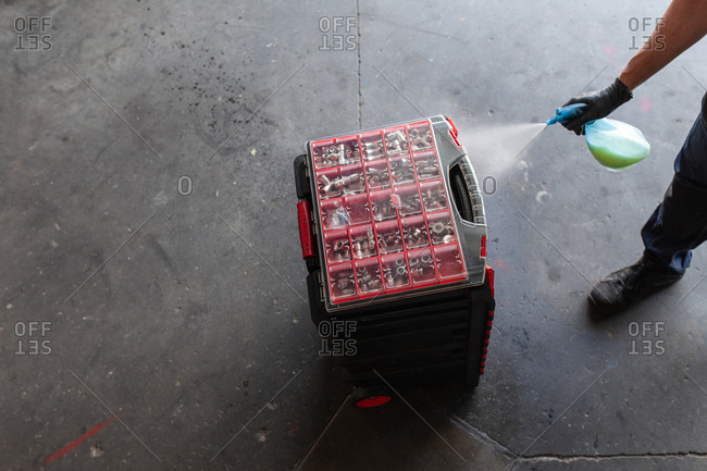 Unrecognizable male mechanic spraying tool box with detergent during work in professional garage