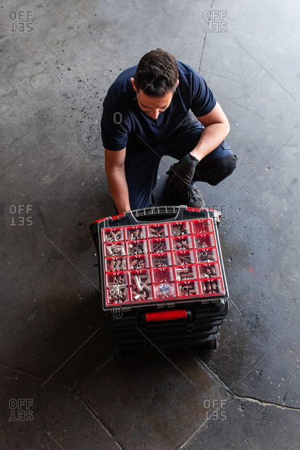 From above male mechanic spraying tool box with detergent during work in professional garage