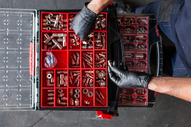 Top view of anonymous mechanic in gloves sorting various nuts and screws inside tool box during work in garage