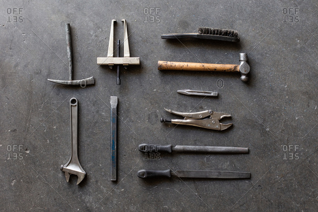 Top view of assorted shabby repair tools placed on grungy gray floor of workshop