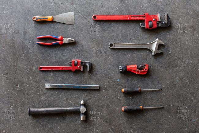 Top view of shabby metal repair tools arranged in rows on floor of garage