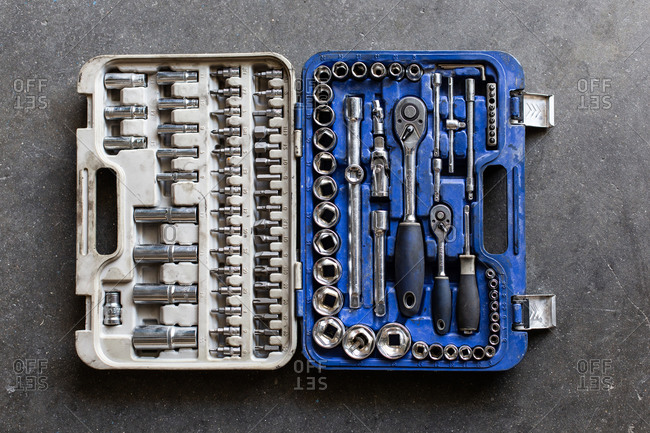 Top view of kit of metal wrenches and bits placed inside plastic box on garage floor