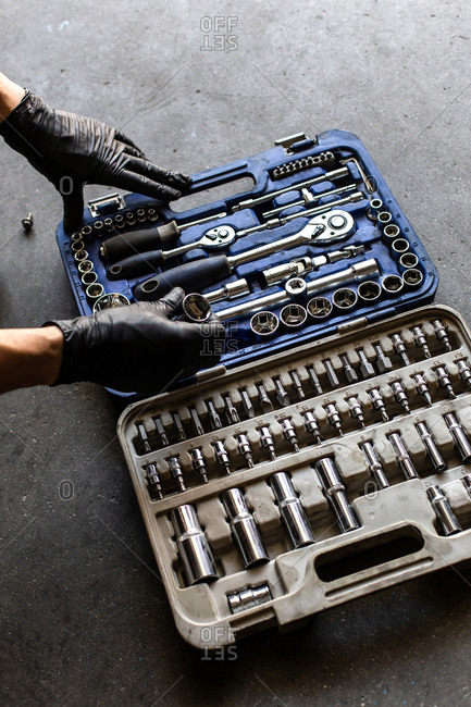 From above anonymous male technician in latex gloves selecting wrench bit from tool box during work in garage