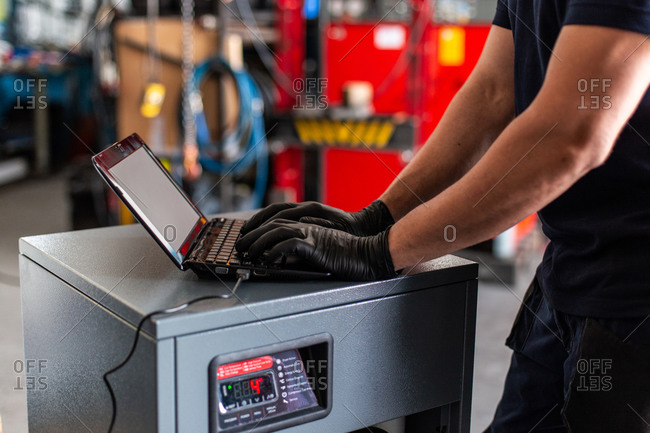 Adult man in using laptop to program broken machine during work in modern workshop