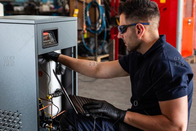 Adult man in goggles using laptop to program broken machine during work in modern workshop