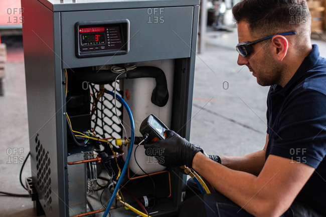 Male mechanic in goggles and gloves using voltage tester on modern machine during work in workshop