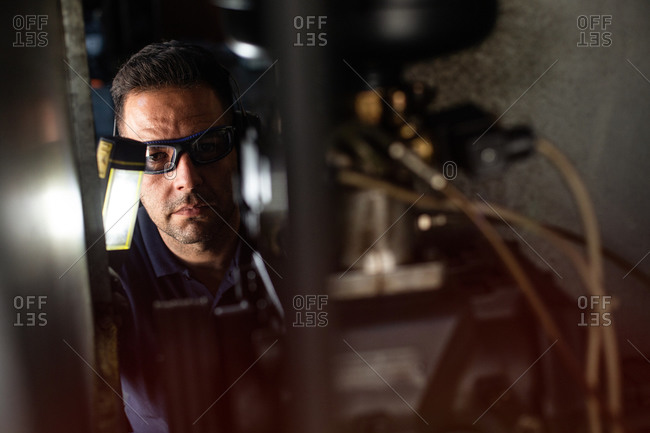 Professional male mechanic in protective glasses and headphones using flashlight while checking details of machine during repair works in workshop