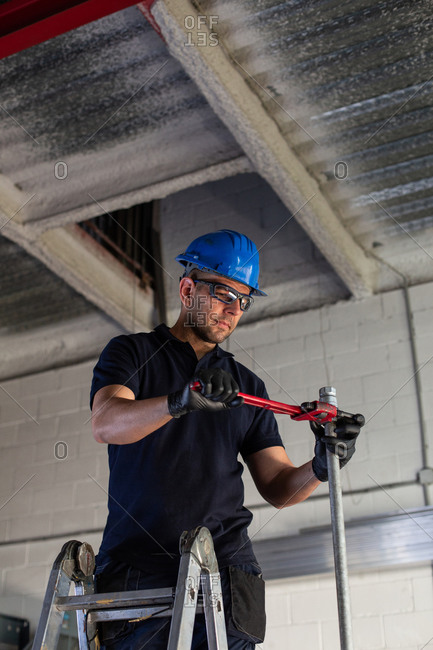 Low angle of cheerful male worker in hardhat and protective glasses standing on ladder and installing metal pipe with plumber wrench while working in workshop