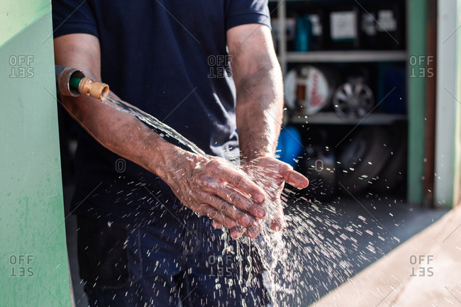 Crop anonymous male workman washing hands under tap with water after finishing work in repair service workshop