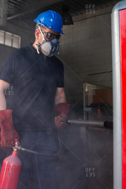 Professional male master in respirator and protective hardhat and gloves using fire extinguisher while working in workshop